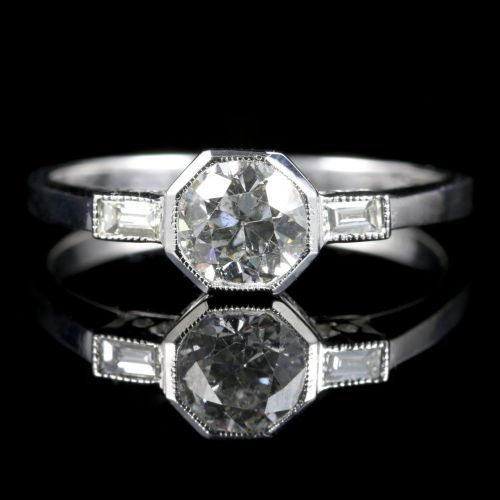 A stunning antique engagement ring in 18ct white Gold which boasts a 0.90ct central Old Cut Diamond with baguette cut Diamond shoulders.