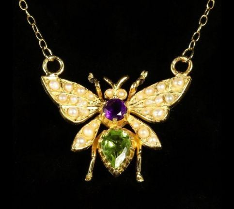 BUTTERFLY SUFFRAGETTE PENDANT NECKLACE PERIDOT PEARL AND AMETHYST CLOSE UP